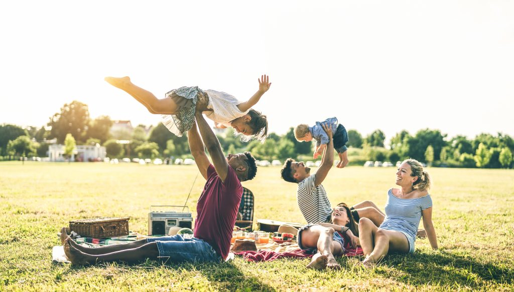 Young multiracial families having fun playing with kids at pic nic barbecue party - Multicultural joy and love concept with mixed race people together with children at park - Warm contrasted filter