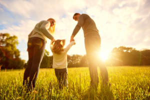 Parents with their child in a sunny field