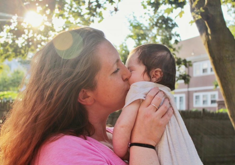 woman holding and kissing young baby